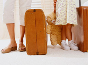 Children with suitcases and teddy bear
